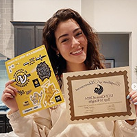Female student holding Top 10 Knights Award and stickers