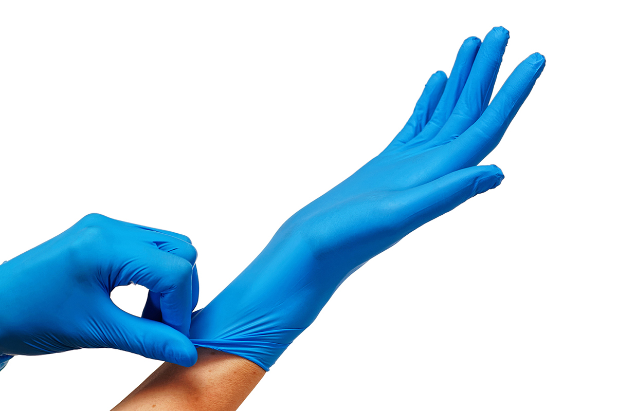 Doctor putting on protective blue gloves isolated on white background